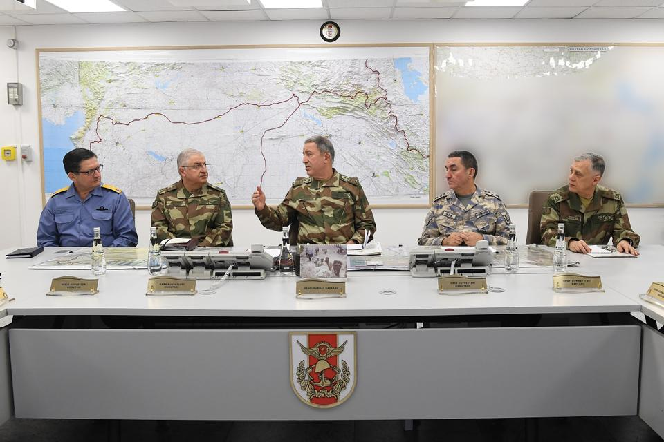 Turkey's Chief of General Staff General Hulusi Akar (C) discussing