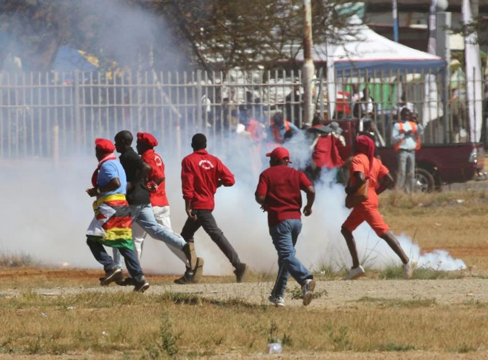 People flee teargas as opposition party supporters clash with police in Harare, Zimbabwe.