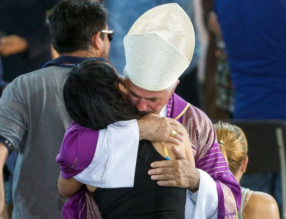 Giovanni D'Ercole, bishop of Ascoli Piceno, hugs a woman after a funeral service for victims of the earthquake inside a gym, Italy August 27, 2016.