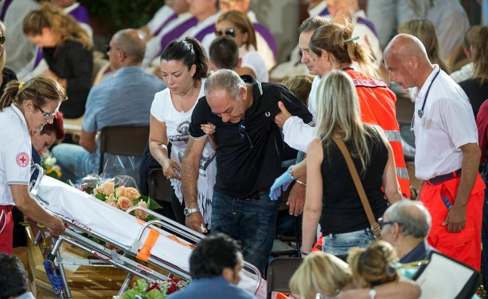 A man is helped by Red Cross members during a funeral service for victims of the earthquake inside a gym in Ascoli Piceno, Italy August 27, 2016.