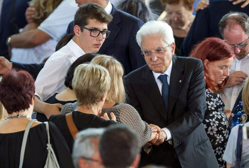 Italian President Sergio Mattarella shakes hands with a woman after a funeral service for victims of the earthquake inside a gym in Ascoli Piceno, Italy. August 27, 2016.