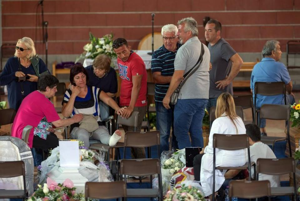 Mourners pay their respects as they attend a funeral for the earthquake victims inside a gym in Ascoli Piceno August 27, 2016.