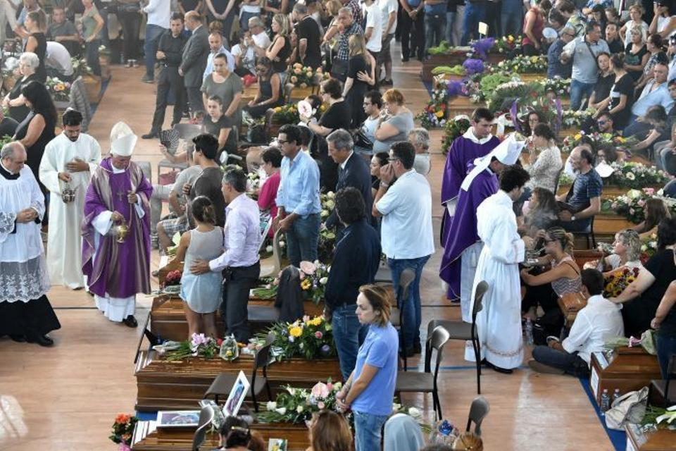 People gather during a funeral service for victims of the earthquake inside a gym in Ascoli Piceno, Italy August 27, 2016.