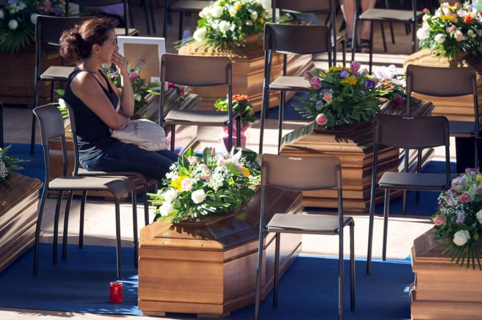A woman sits next to a coffin to pay her respects as she attends a funeral for the earthquake victims inside a gym in Ascoli Piceno August 27, 2016.
