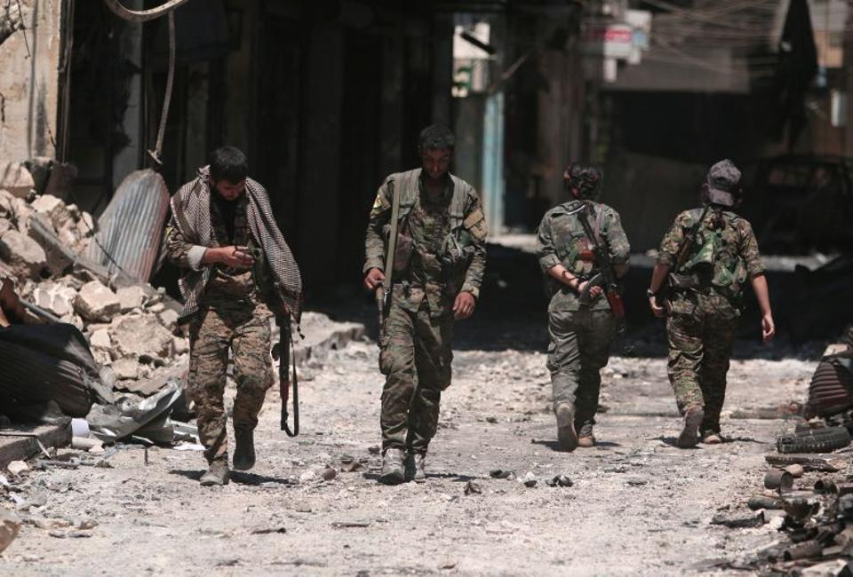 Militants of the Syrian Democratic Forces (SDF) walk on the rubble of damaged shops and buildings in the city of Manbij, in Aleppo Governorate, Syria, on August 10, 2016. Image: Reuters