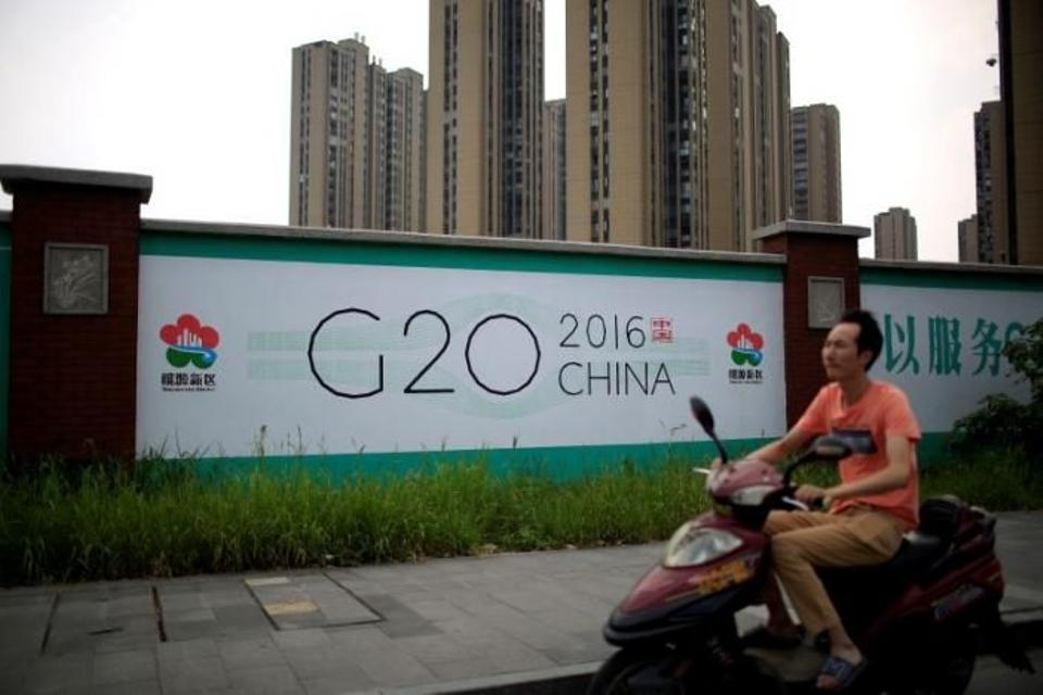 A man rides an electronic bike past a billboard for the upcoming G20 summit in Hangzhou, Zhejiang province, China, July 29, 2016. Image: Reuters.