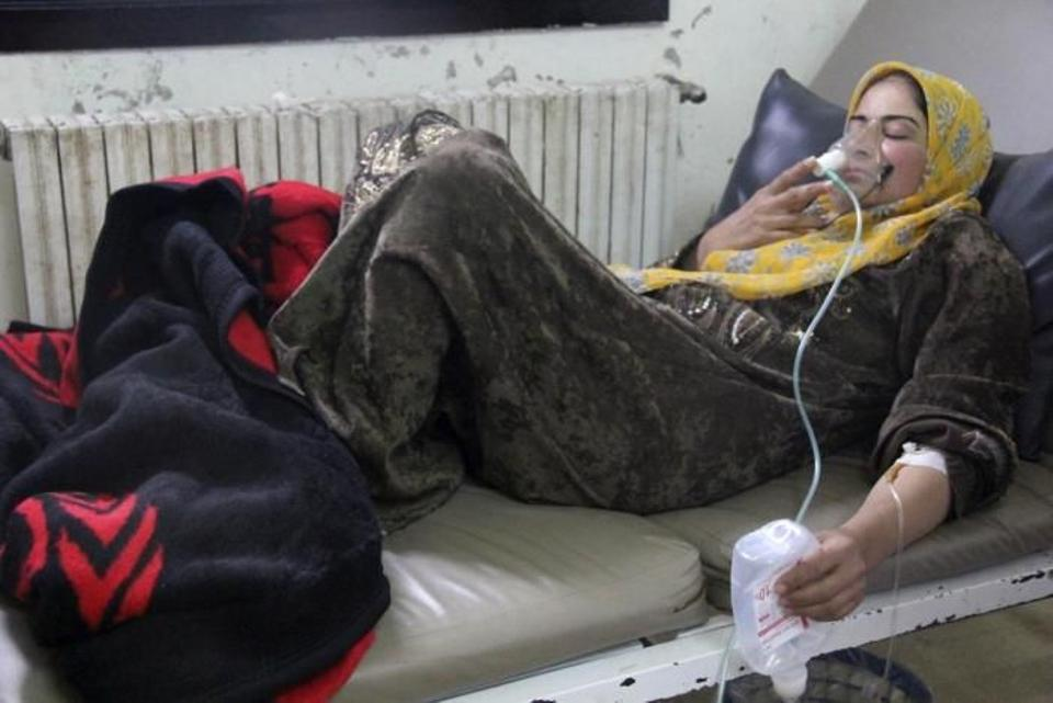 A woman, affected by what activists say was a gas attack, breathes through an oxygen mask inside a field hospital in Kfar Zeita village in the central province of Hama April 12, 2014.