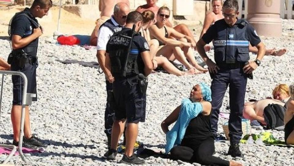 Woman on Nice beach being forced to remove her burkini by armed police, August 23, 2016. Image: AFP.