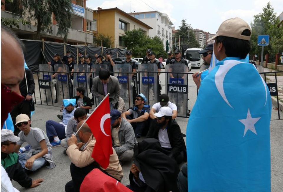 Riot police stand as a group of Uighur protesters demonstrate outside the Thai embassy in Ankara, Turkey. Thailand sent back to China more than 100 ethnic Uighur refugees on Thursday, drawing criticism from the UN refugee agency and human rights groups.