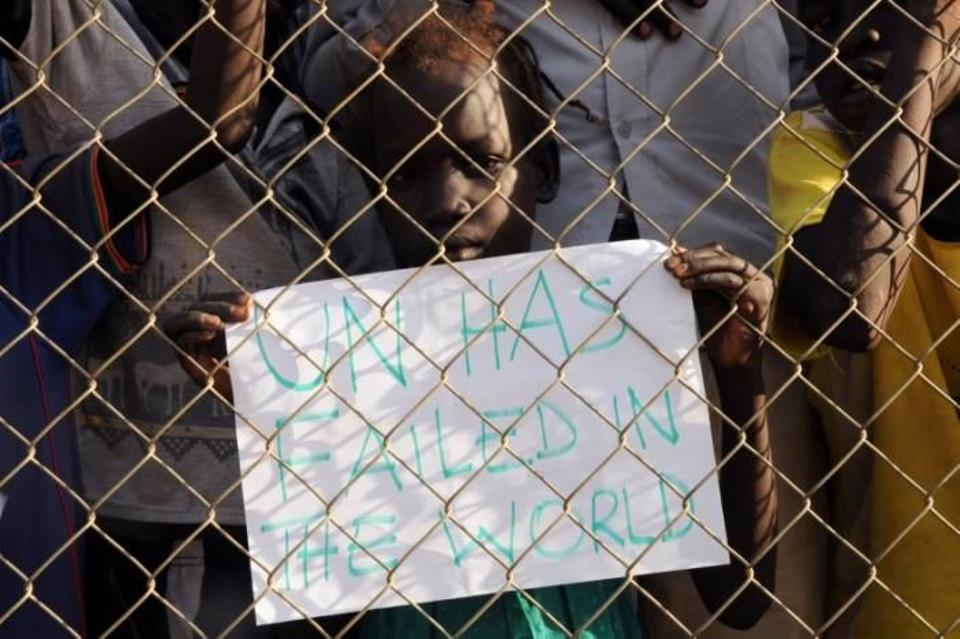 A child displaced in the recent fighting, holds a placard behind the fence at demonstration during a visit by the United Nations Security Council, delegation to the UN House in Jebel, near South Sudan's capital Juba, September 3, 2016