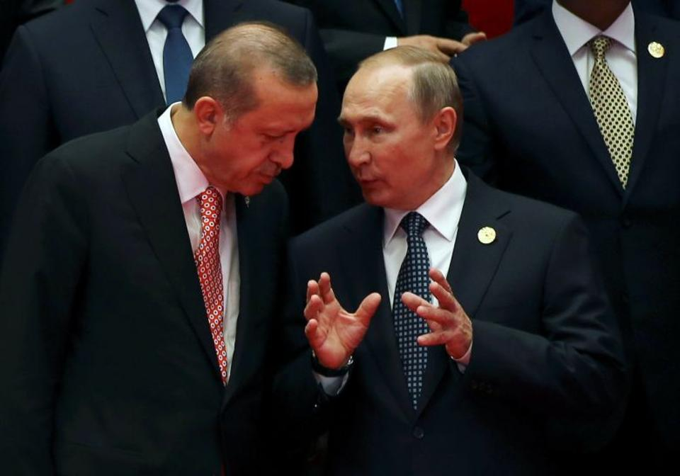 Russian President Vladimir Putin talks with Turkey's President Erdogan as they pose for a group picture during the G20 Summit in Hangzhou, China.