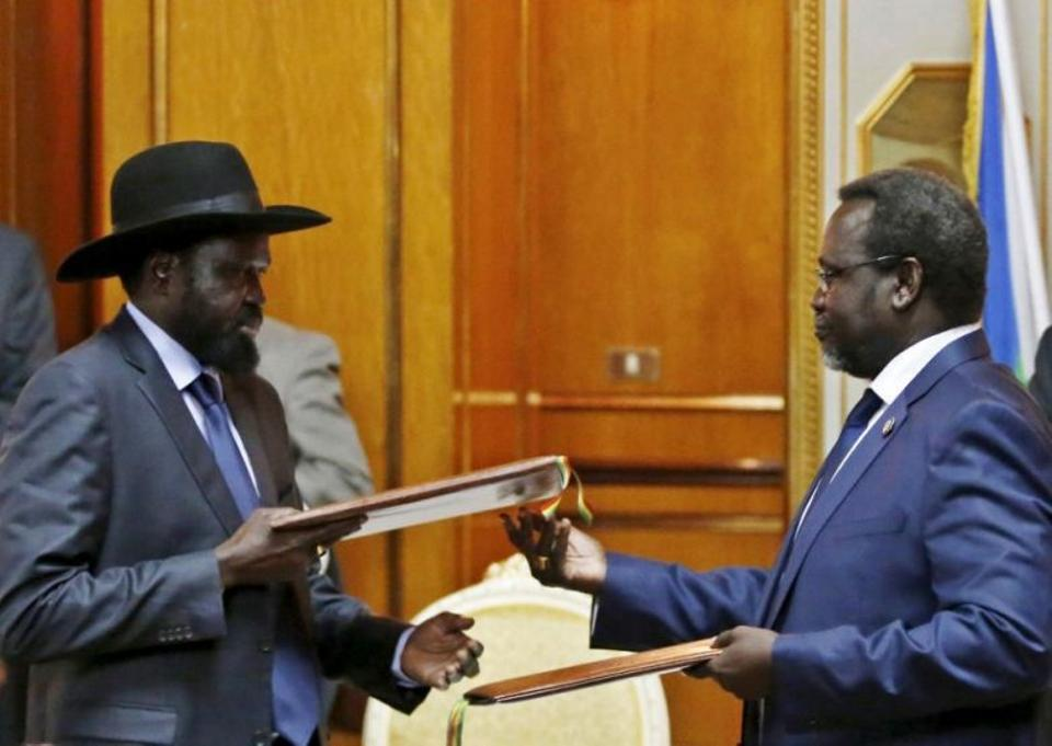 South Sudan's rebel leader Riek Machar (R) and South Sudan's President Salva Kiir exchange signed peace agreement documents in Addis Ababa in this May 9, 2014 file photo.