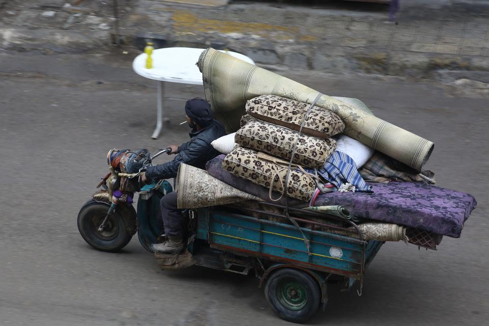 A man is seeing trying to flee from eastern Ghouta with his family's belongings strapped to a cart on his motorbike.