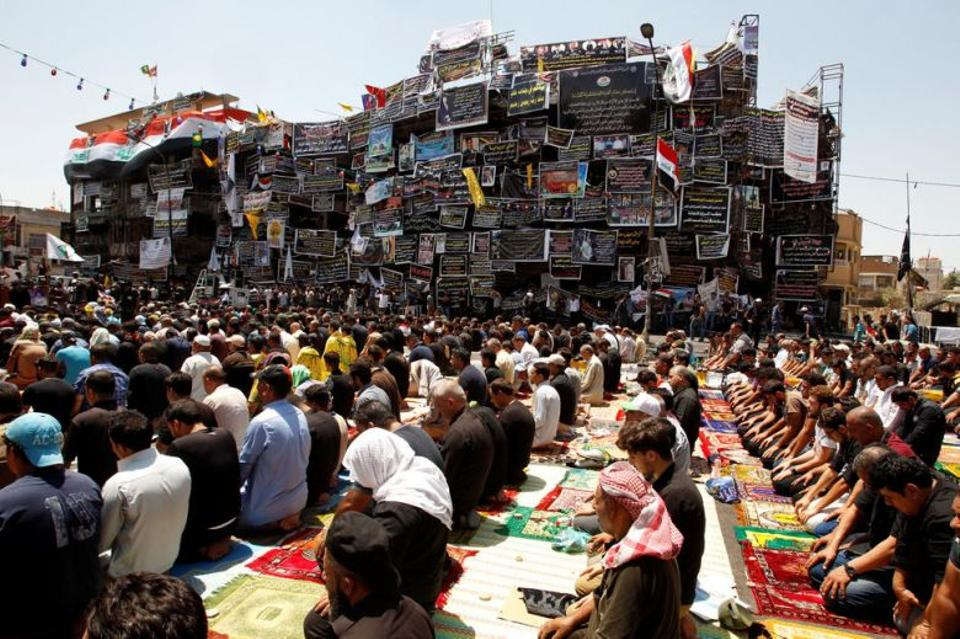 Iraqis attend Friday prayers during Eid al-Fitr at the site of July's car bomb attack in Baghdad.