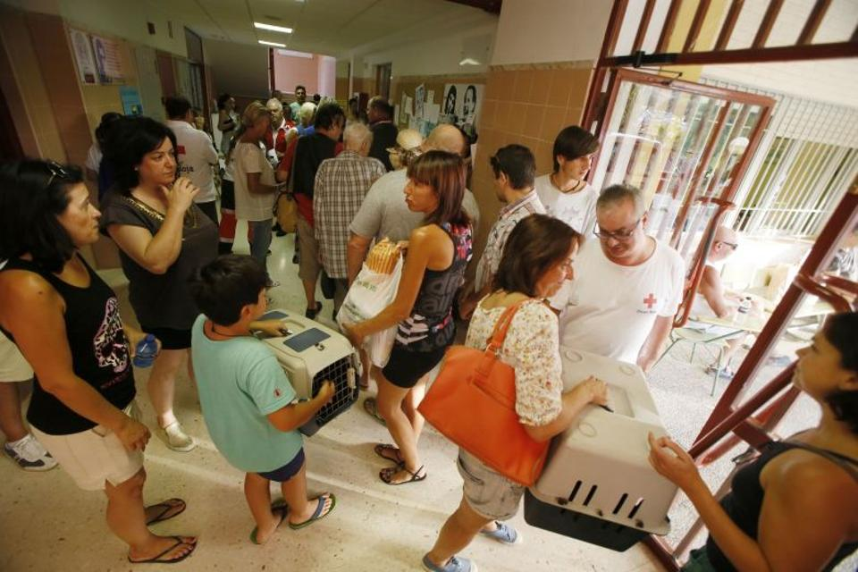 People arrive at the Antoni Lledo institute after evacuating their homes due to forest fires along the coastline in the Spanish resort of Javea, Valencia region, on September 5, 2016.