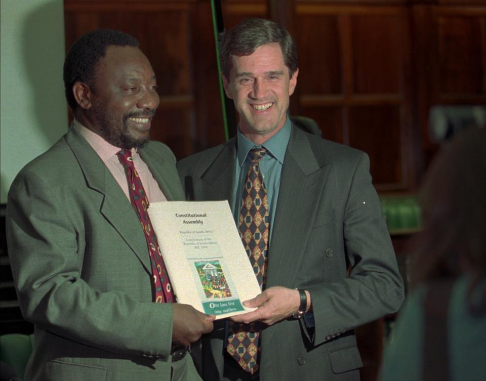 Chairman of the Constitutional Assembly Cyril Ramaphosa, and main National Party negotiator, Roelf Mayer, pose with a printed copy of the draft of the new South African Constitution after the last session at the Parliament in Cape Town, May 8, 1996. (File photo)