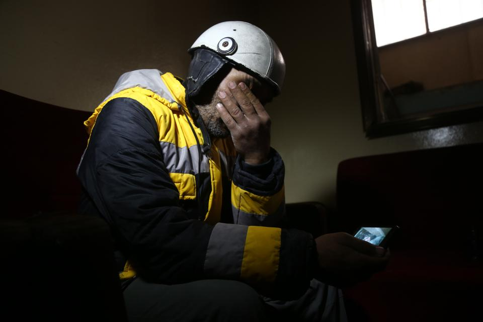 Samir Salim mourns as he looks at a picture that he took when he tried to rescue his mother from under the rubble of his home in the town of Medeira in Syria's opposition-held Eastern Ghouta area. February 12, 2018.