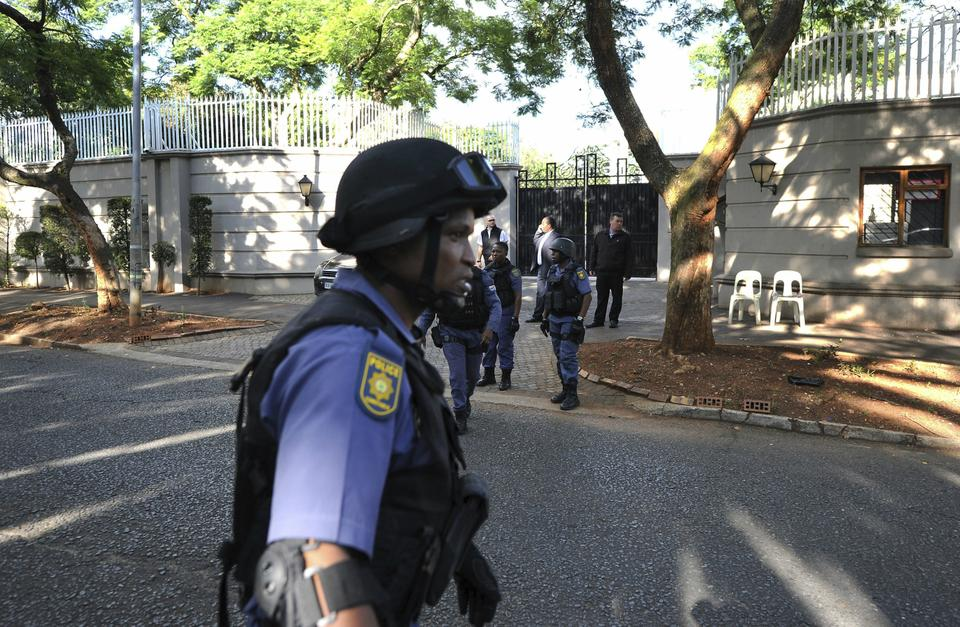 South African police exit after a raid on a home in Johannesburg on Wednesday. The police raided the home of a business family linked to President Jacob Zuma as the nation awaited word from the embattled leader on whether he will obey a ruling party order to quit.