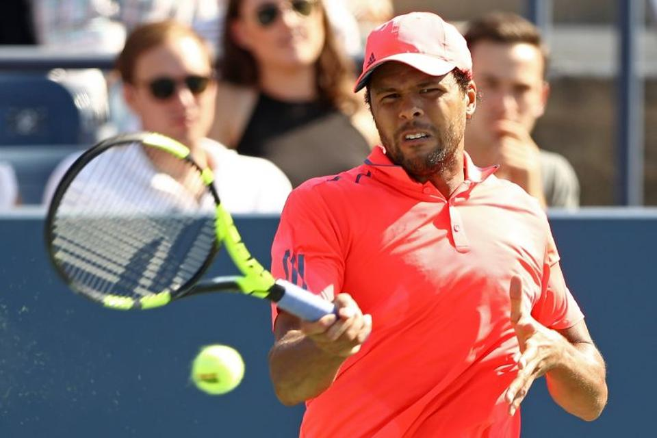 Jo-Wilfried Tsonga of France returns a shot to Jack Sock of the United States during his fourth round Men's Singles match on Day Seven of the 2016 US Open.