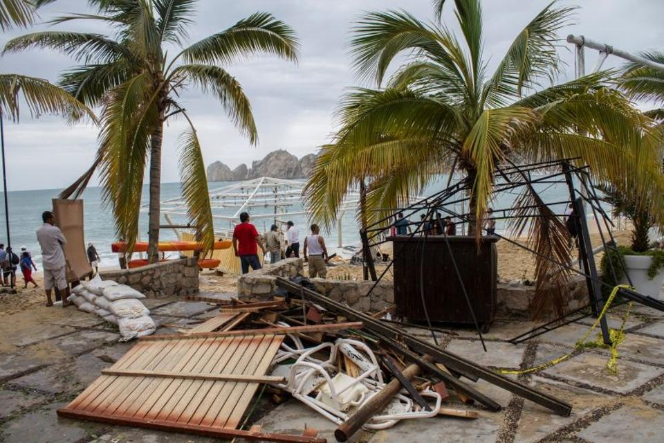 Residents stand next to debris of a restaurant in the aftermath of Hurricane Newton in Los Cabos, Mexico, September 6, 2016.