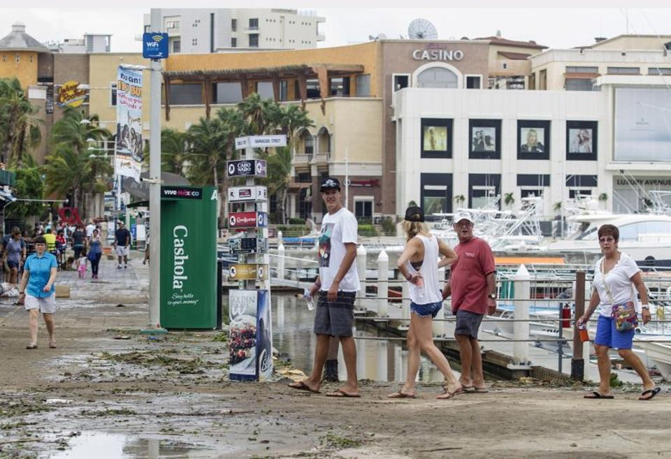 Tourists walk around the area affected by Hurricane Newton in Los Cabos, Baja California Sur tate, Mexico, on September 6, 2016.