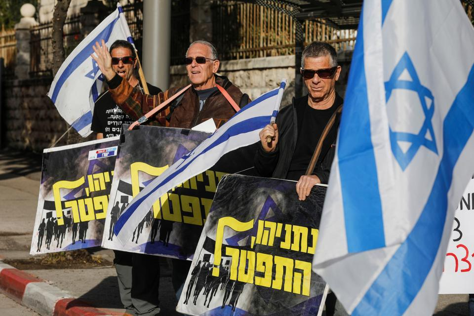 Israeli protesters wave national flags and hold signs reading in Hebrew