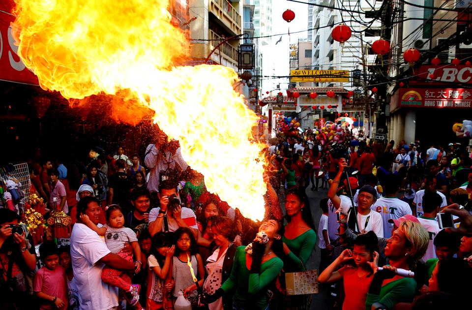 A fire-eater performs on the street in celebration of the Chinese Lunar New Year, February 16, 2018 at Manila's Chinatown district, Philippines.