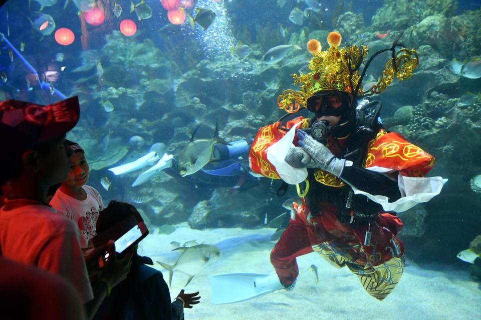 A diver dressed in Fortune God costume greets to visitors after he fed fish as part of Chinese Lunar New Year celebrations at Aquaria KLCC underwater park in Kuala Lumpur, Malaysia, February 16, 2018.