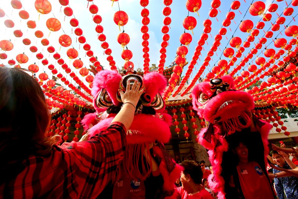 Temple visitors play with the lion dance troupe during its performance on the first day of Chinese Lunar New Year at a temple in Kuala Lumpur, Malaysia, February 16, 2018.