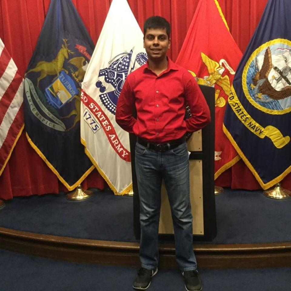Standing before a Marine podium, Raheel Siddiqui adopts the standard