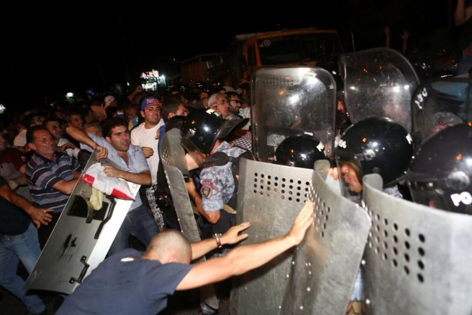 Riot police clash with demonstrators who had gathered in a show of support for gunmen holding several hostages in a police station in Yerevan, Armenia, July 20, 2016.