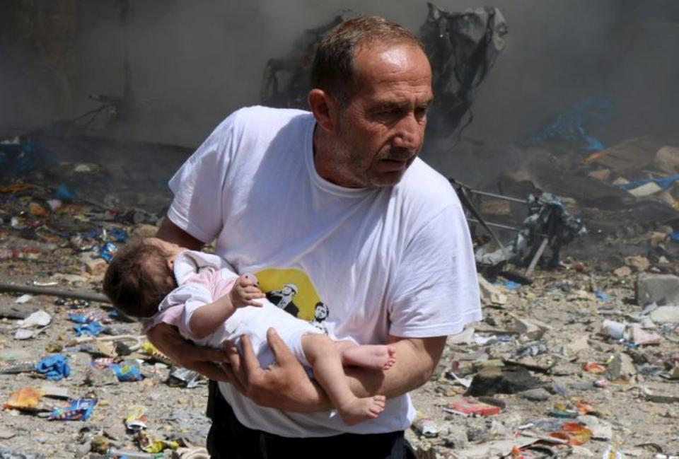 A man holds a baby who survived what activists said was a barrel bomb dropped by forces loyal to Syrian regime leader Bashar al-Assad, at a site in the city of Aleppo. Source: Reuters