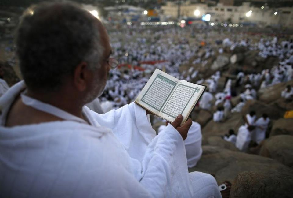 A Muslim pilgrim reads a copy of the Koran, Islam's holy book, as he joins one of the Hajj rituals on Mount Arafat near Mecca early on September 11, 2016.