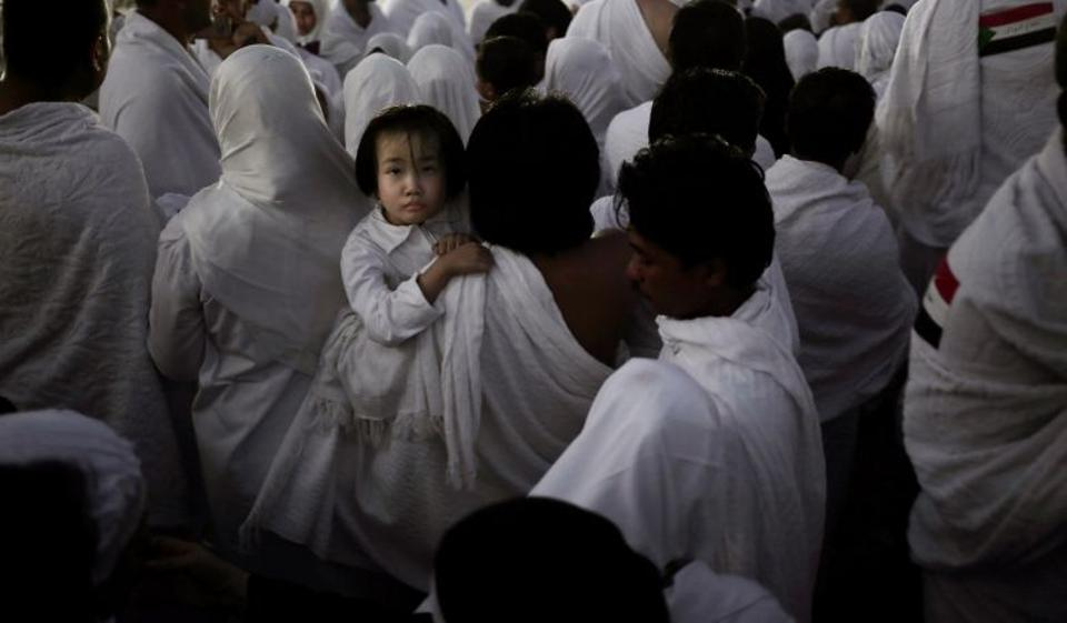 An Indonesian father carries his daughter through the crowd after reaching the top of a rocky hill known as Mountain of Mercy, on the Plain of Arafat, during the annual hajj pilgrimage.