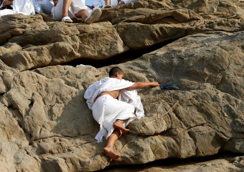 A boy climbs Mount Mercy on the plains of Arafat during the annual haj pilgrimage, outside the holy city of Mecca, Saudi Arabia September 11, 2016.