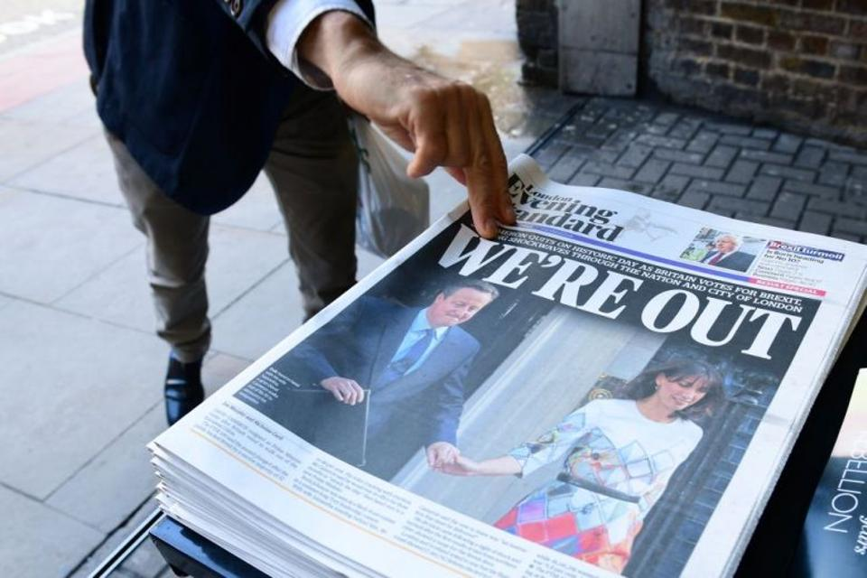 This file photo taken on June 24, 2016 shows a man picking up a copy of the London Evening Standard with the front page reporting the resignation of British Prime Minister David Cameron and the vote to leave the EU in a referendum,