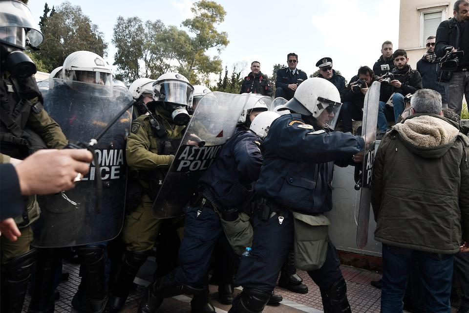 Police push back a protester during a demonstration against an educational reform law to be voted in front of the Greek parliament in central Athens on February 26, 2018.