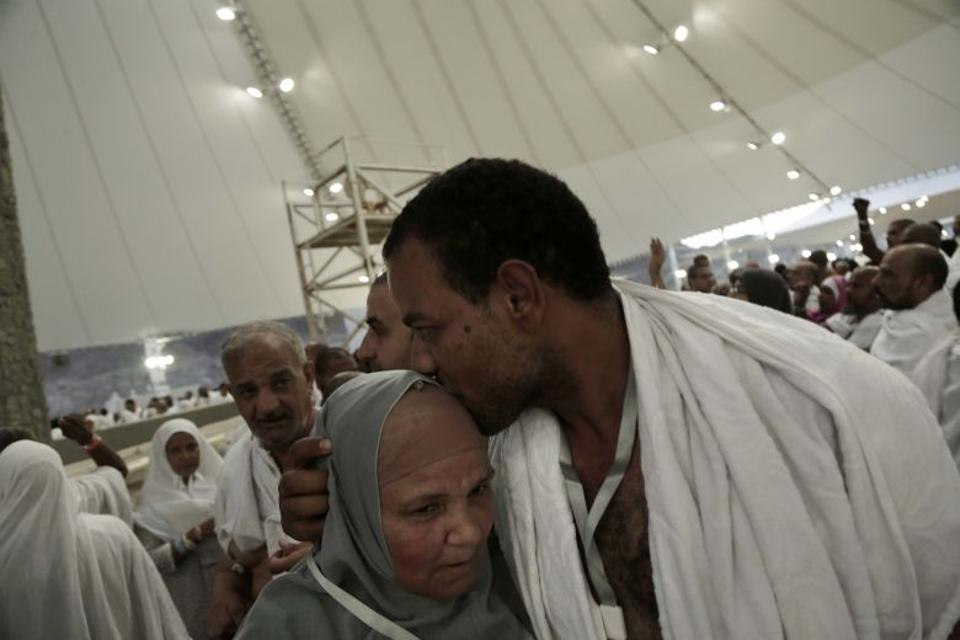 An Egyptian man kisses his mother's forehead of she cast stones at a pillar symbolizing the stoning of Satan, in a ritual called