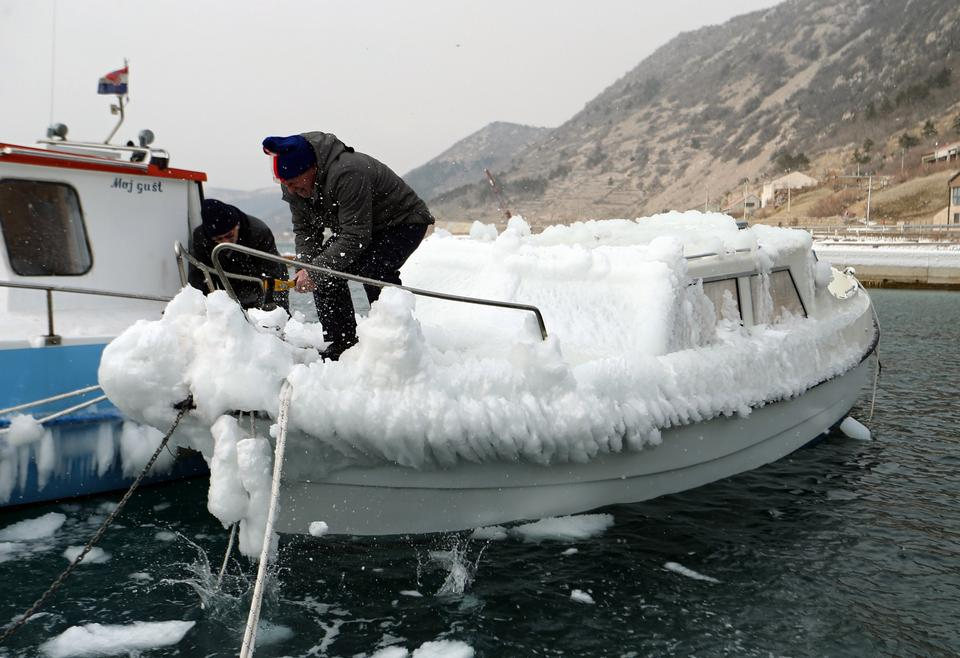 A man cleans a boat covered with ice in Bakarac, Croatia on February 27, 2018.
