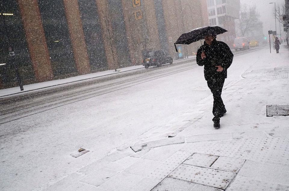 A man carries an umbrella during a snow shower in London, Britain, on February 27, 2018.