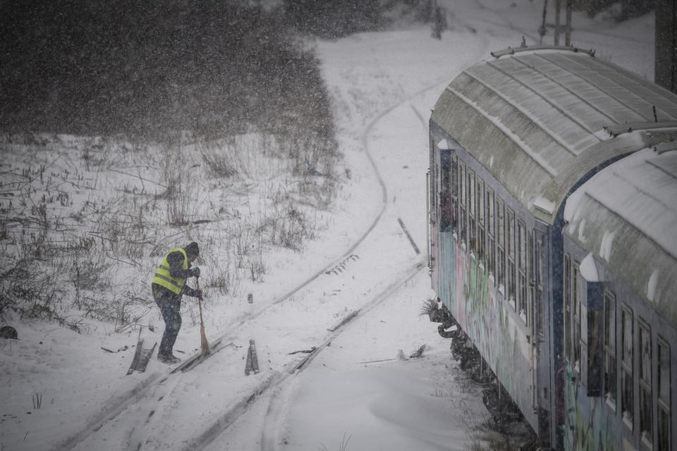 A worker removes snow from a railway switch point close to the North Station in Bucharest, Romania, on February 27, 2018.
