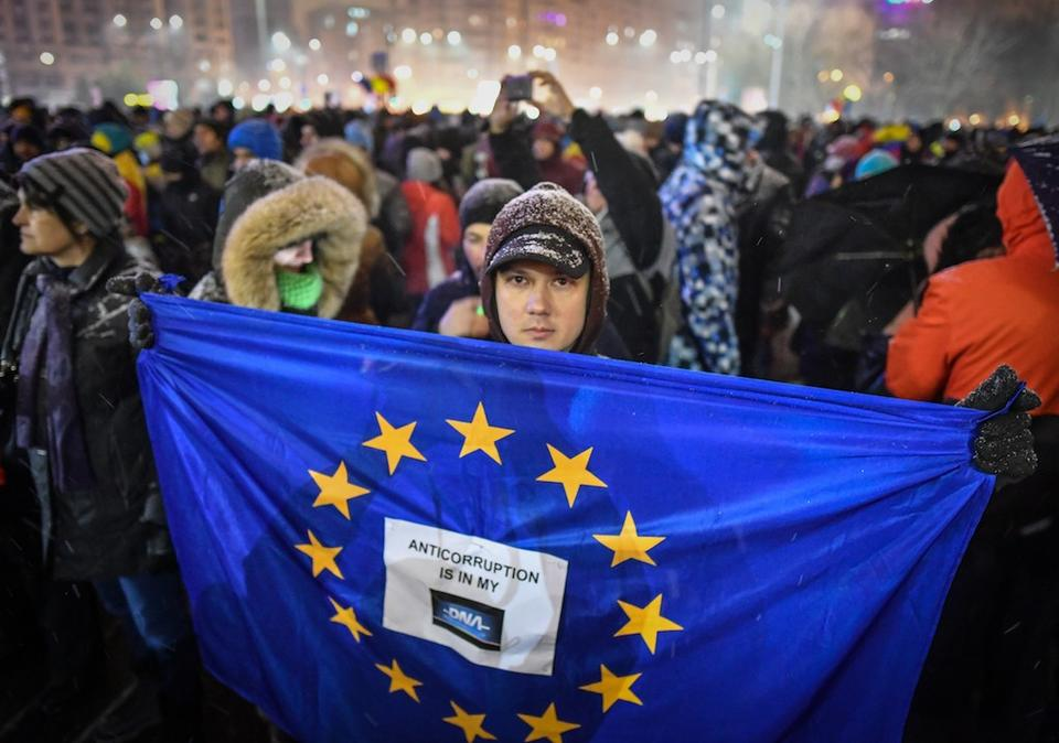 A man holds an EU flag during a protest against the Justice minister and corruption in front of the Romanian Government in Bucharest on February 25, 2018.
