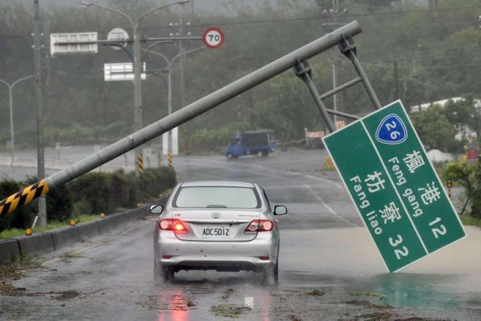 A car drives pass a collapsed traffic sign, toppled by strong winds of typhoon Meranti, as it slashes southern Taiwan. AFP