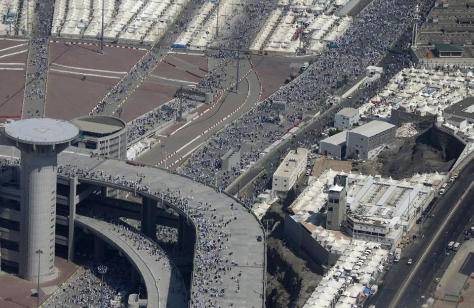 Muslim pilgrims walk towards the location where they throw pebbles at pillars during the