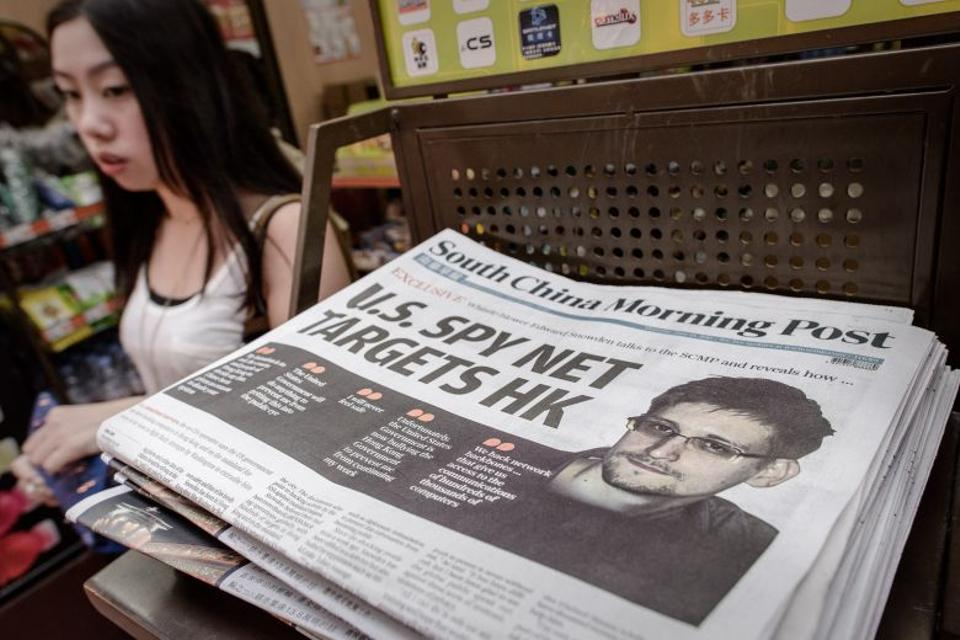This file photo taken on June 13, 2013 shows a woman walking past an edition of the South China Morning Post carrying the story of US intelligence whistleblower Edward Snowden (R) on its front page in Hong Kong.