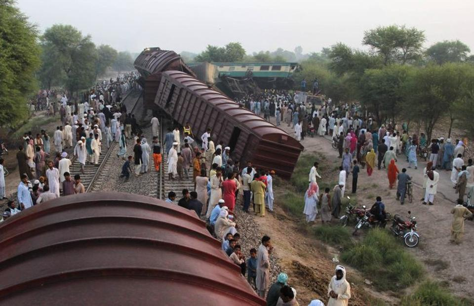 People gather beside the wreckage at the site of the collision of two trains on the outskirts of Multan on September 15, 2016.