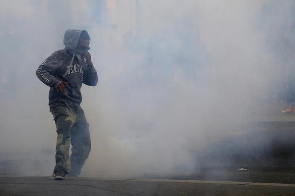 A man runs away from tear gas during clashes with French riot police at a march in Nantes, western France, to demonstrate against the new French labour law, September 15, 2016.