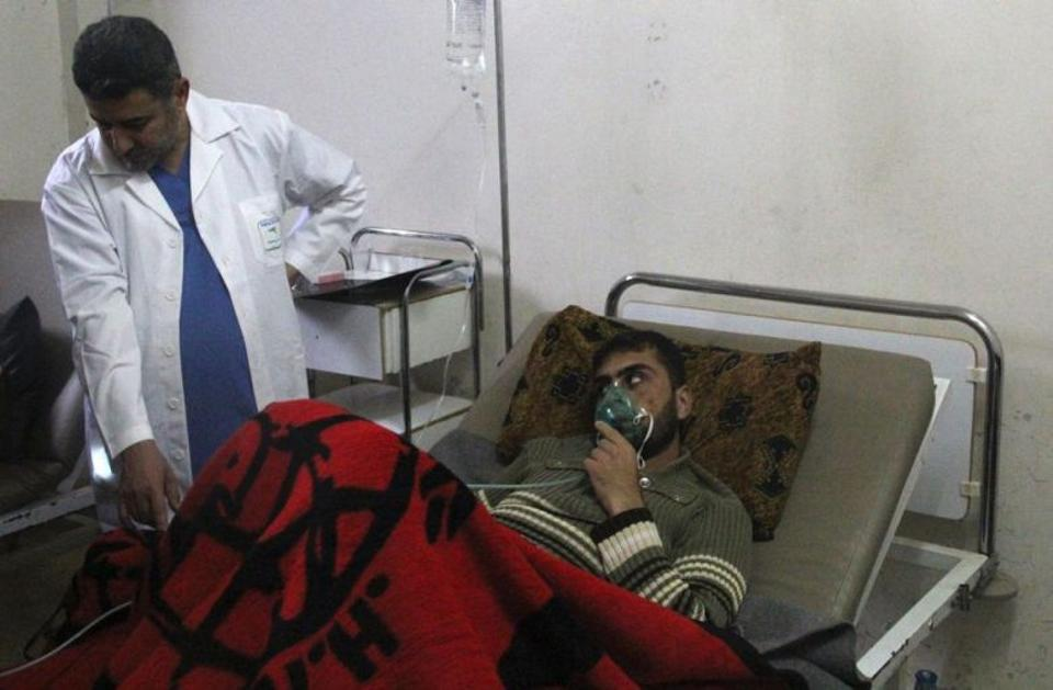 A man, affected by what activists say was a gas attack, breathes through an oxygen mask inside a field hospital in Kfar Zeita village in the central province of Hama April 12, 2014.