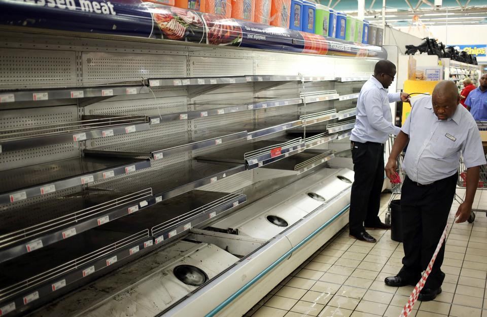 A worker looks at empty shelves after removing processed meat products at a store in Johannesburg.