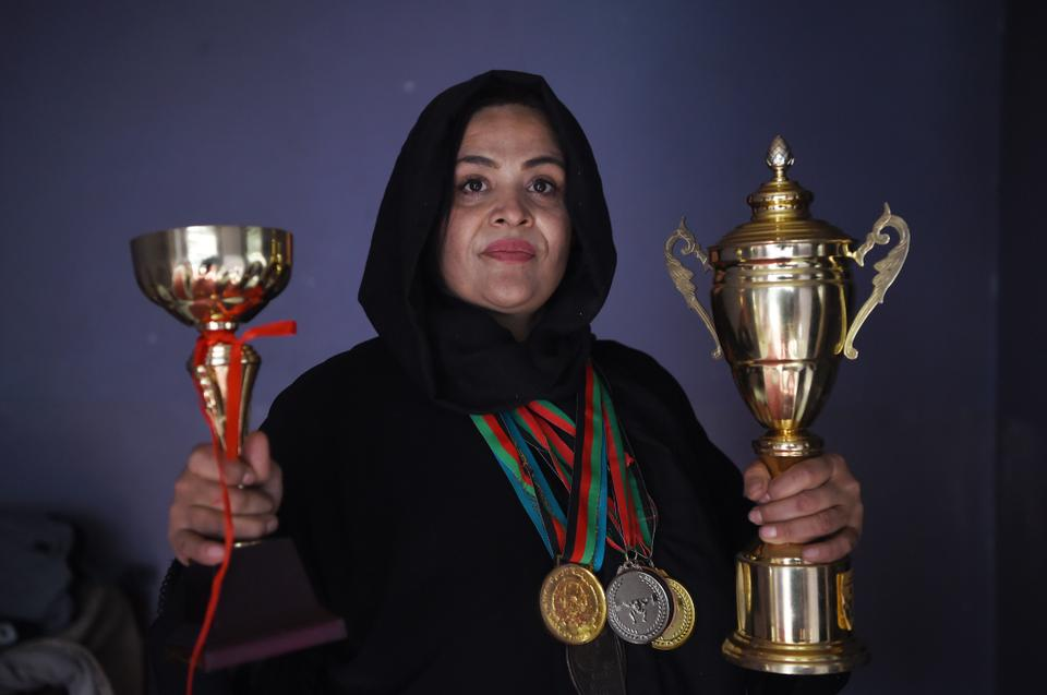 Afghanistan national powerlifting team member Rasheda Parhiz (L), 40, poses for a picture with her trophies and medals at her home in Kabul.